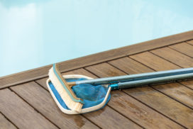 34269889 - wall brush and leaf skimmer maintenance tools on deck beside swimming pool